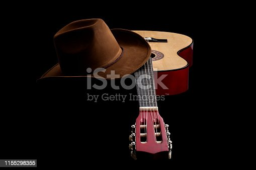istock American culture, folk song and country music concept theme with a cowboy hat and an acoustic guitar isolated on black background with dramatic lighting 1155298355