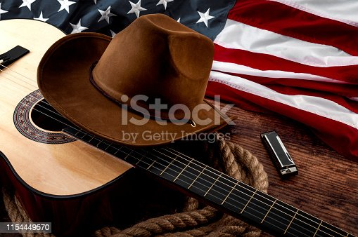 istock American culture, living on a ranch and country music concept theme with a cowboy hat, USA flag, acoustic guitar, harmonica and a rope lasso on a wooden background in a old saloon 1154449570