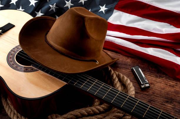 La cultura americana, viviendo en un tema conceptual de la música country y el rancho con un sombrero de vaquero, bandera de los E.E.U.U., guitarra acústica, armónica y un lazo de la cuerda sobre un fondo de madera en un viejo salón - foto de stock