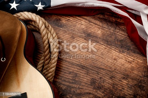 istock American culture, living on a ranch and country music concept theme with a cowboy hat, USA flag, rope lasso and acoustic guitar on a wooden background in a old saloon with copyspace 1154450110