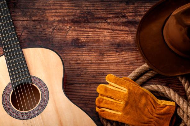 Cultura americana, vivir en un tema de concepto de rancho y música country con un sombrero de vaquero, guitarra acústica, guantes de granja y un lazo de cuerda sobre un fondo de madera en un antiguo salón con espacio de copia - foto de stock