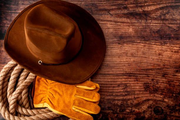 Cultura americana, vivir en un rancho o granja y música country concepto tema con un sombrero de vaquero, lazo de cuerda y guantes de cuero rodeo sobre un fondo de madera en un antiguo salón con espacio de copia - foto de stock