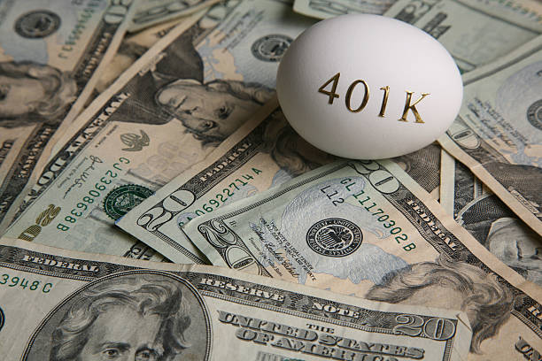 American currency and an egg with '401K' on it investing money for retirement 401k stock pictures, royalty-free photos & images
