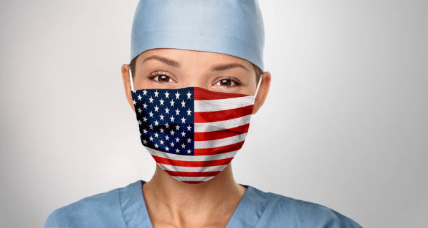 USA American doctor wearing Coronavirus pandemic COVID-19 mask in the United States of America. American flag print on Asian woman doctor's mask smiling in confidence giving hope stock photo
