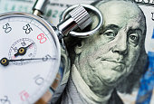 istock American dollar and stop watch 855050420