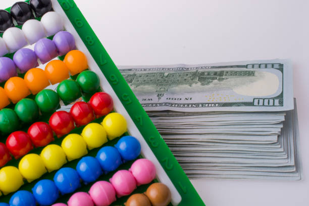 American dollar banknotes by the side of a colorful abacus stock photo