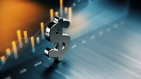 American Dollar Symbol Standing On Wood Surface In Front Of A Graph — стоковые фотографии и другие картинки Американская валюта