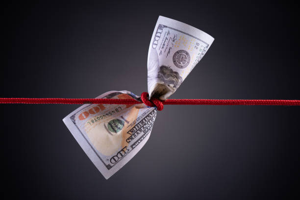 American dollar tied up in red rope knot on dark background with copy space. business finances, savings and bankruptcy concept. American dollar tied up in red rope knot on dark background with copy space. business finances, savings and bankruptcy concept. recession stock pictures, royalty-free photos & images