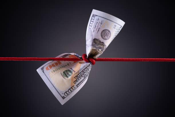 미국 달러 복사 공간 어두운 배경에 빨간 밧줄 매듭에 묶여. 비즈니스 재정, 저축 및 파산 개념. - 불황 뉴스 사진 이미지
