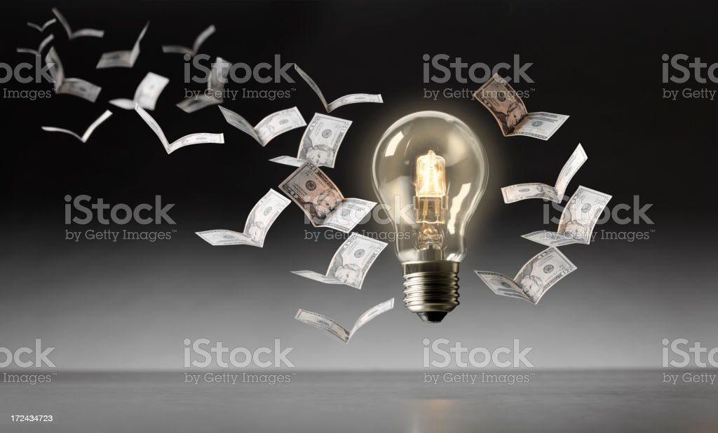 American Dollars Flying Towards the Electric Light Bulb stock photo