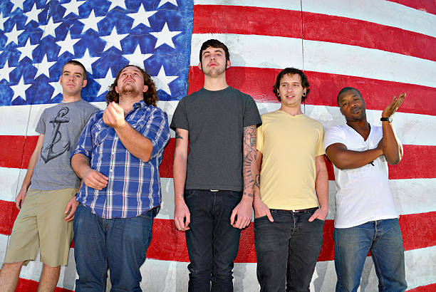 American Dudes A group of young men in their early 20's in front of an American flag.  Linearly corrected fisheye image. american flag tattoos for men stock pictures, royalty-free photos & images