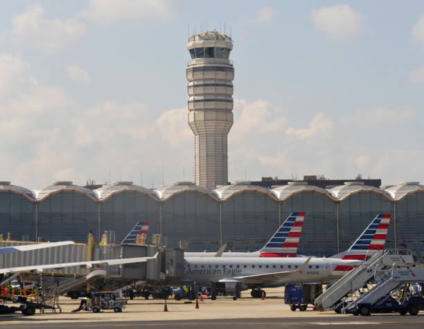 American Eagle aircraft loads passengers and cargo ARLINGTON COUNTY, VIRGINIA—SEPTEMBER 2017: An American Eagle aircraft loads passengers and cargo with the control tower of Ronald Reagan Washington National Airport in the background. ronald reagan washington national airport stock pictures, royalty-free photos & images