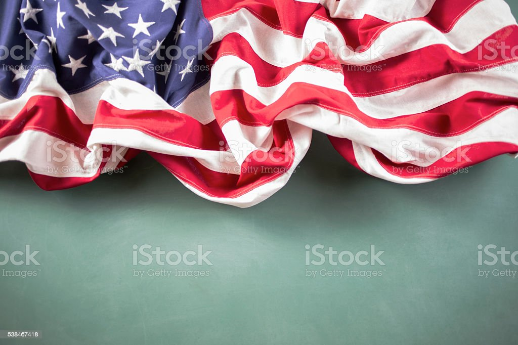 American education. USA flag in front of school classroom chalkboard. stock photo