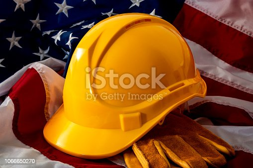 istock American employment in construction, Labor day and industrial work concept with close up on a yellow hard hat and safety gloves on the USA flag 1066650270