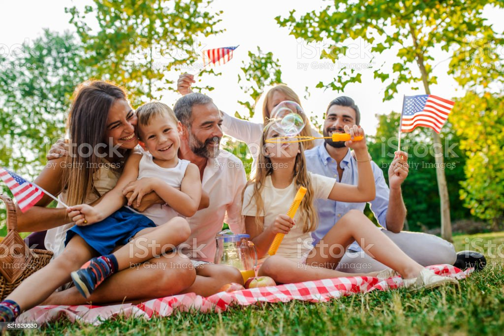 American family blowing bubbles in park stock photo