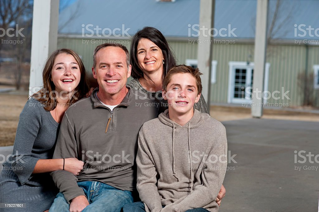 American family on home porch with happy smiles stock photo