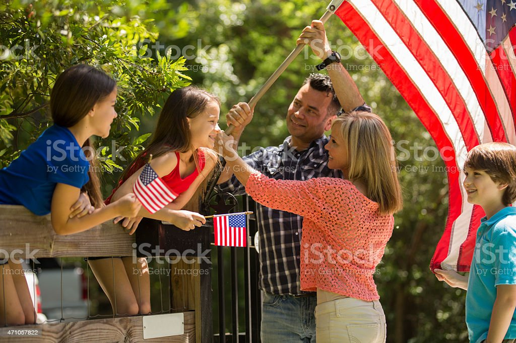 American family puts up USA flag on home fence. Outdoors. stock photo