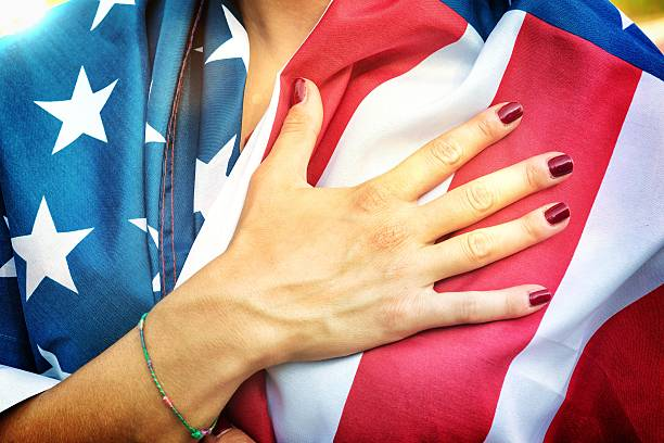 american fan putting hand on hearth during the national anthem - national anthem stock photos and pictures