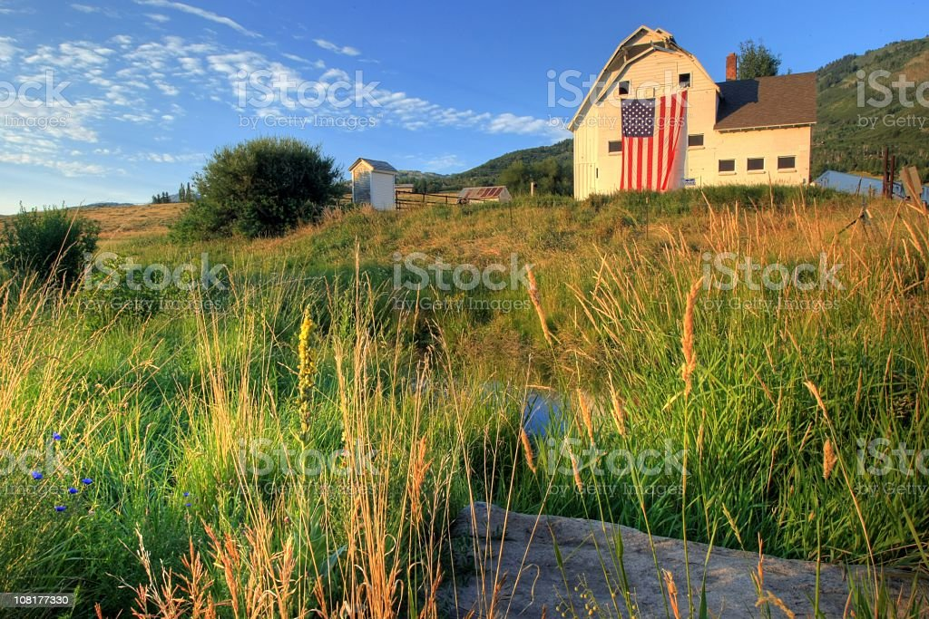 American farm with giant flag in field stock photo