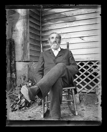 Beautiful Black and White portrait of an American Farmer wearing Victorian-era clothing. Taken on the front porch of his farmhouse dressed in his best clothes--probably on a Sunday afternoon. The image was digitally restored from a glass plate taken circa 1890.