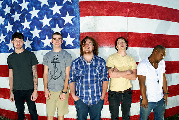 American Fellows A group of young men in their early 20's in front of an American flag.  Linearly corrected fisheye image. american flag tattoos for men stock pictures, royalty-free photos & images