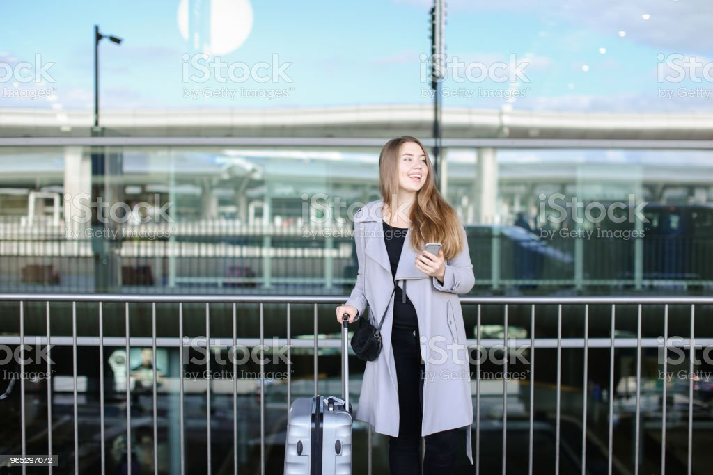 American female person standing with valise and smartpone near airport royalty-free stock photo