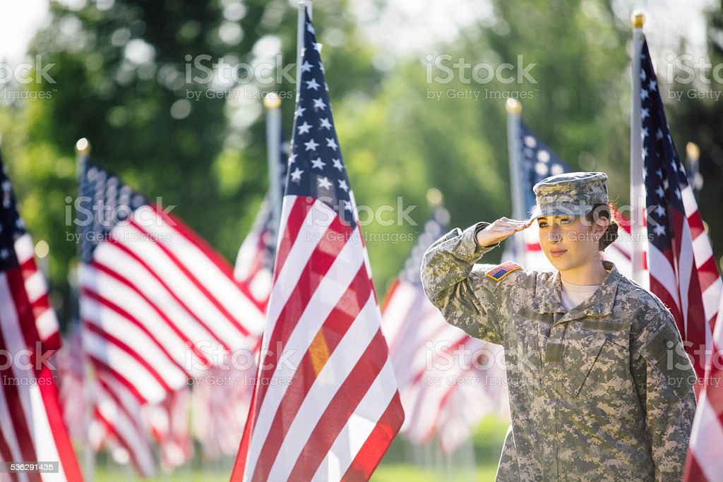 American Female Soldier saluting in front of American Flags stock photo