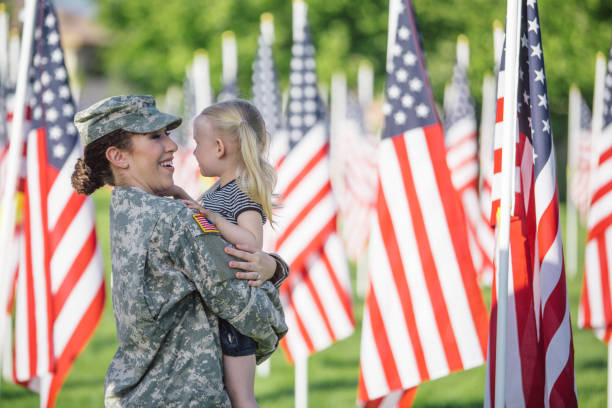 american female soldier with 3 year old girl - veterans day стоковые фото и изображения