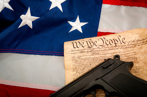 istock American Flag, a handgun and the US constitution 539357008
