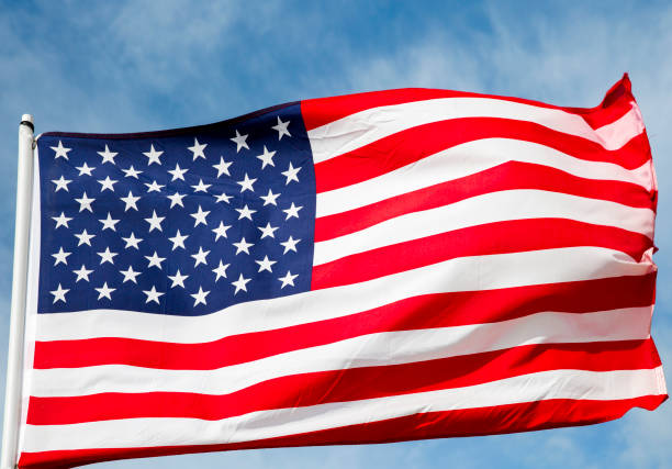 American Flag Against a Blue Cloud Filled Sky stock photo