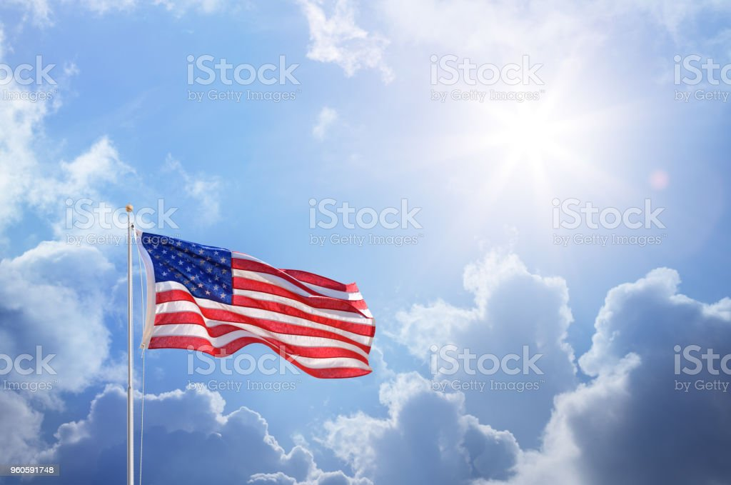 American Flag Against Blue Sky stock photo