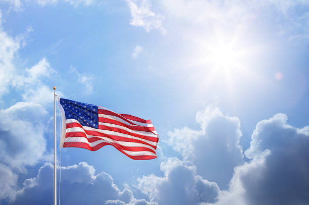 american flag against blue sky - american flag stock pictures, royalty-free photos & images