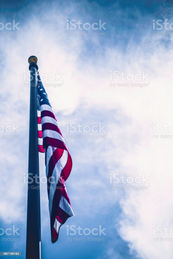 American flag against blue summer sky stock photo