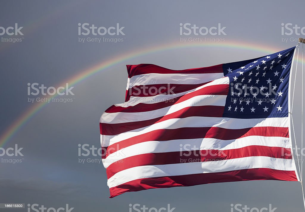 American flag against cloudy sky with a rainbow royalty-free stock photo