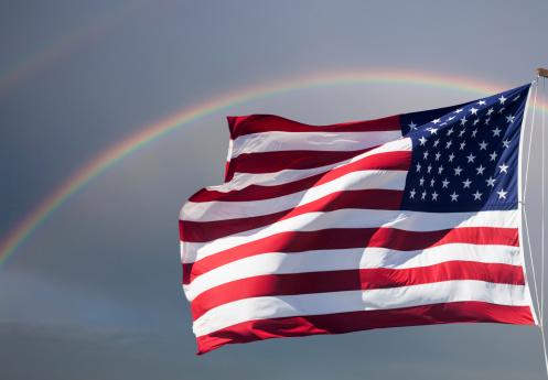 American Flag Against Cloudy Sky With A Rainbow Stock Photo & More Pictures of American Flag