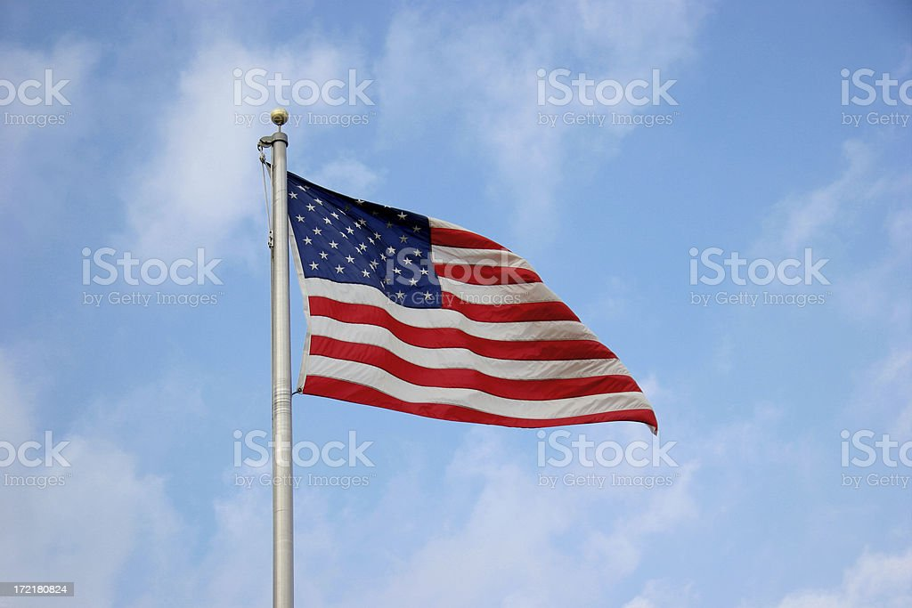 American Flag Against Lightly Clouded Blue Sky royalty-free stock photo