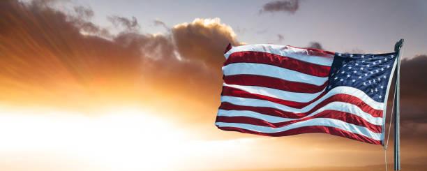american flag against the sky at dusk stock photo