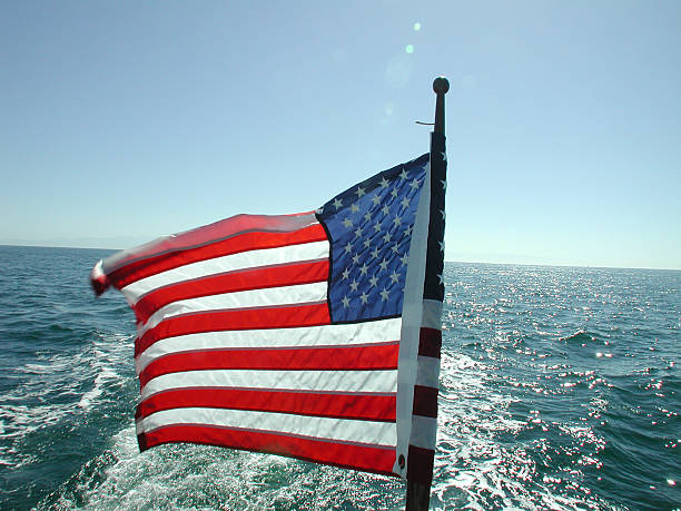 American flag against water and skyline stock photo