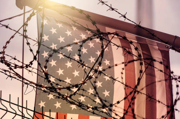 American flag and barbed wire, USA border stock photo