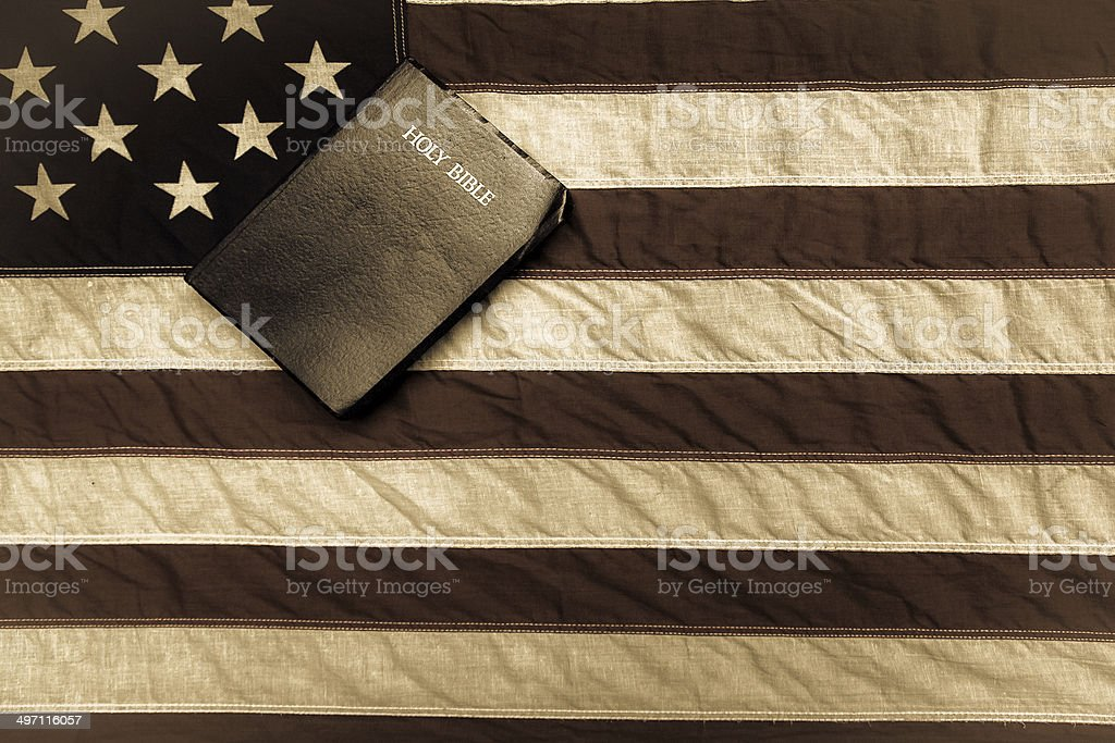 American Flag And Bible King James Bible with a vintage American flag in the background. American Culture Stock Photo