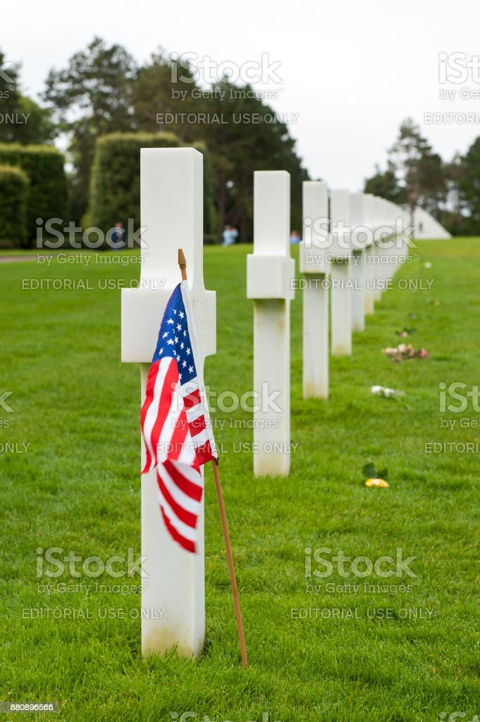 American flag and flowers are left at graves on the Normandy American Cemetery stock photo