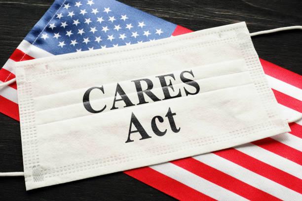 Amerikanische Flagge und Maske mit Zeichen Pflege handeln. Coronavirus Aid, Relief, and Economic Security law concept. – Foto