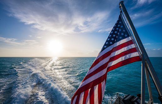American Flag and Sunrise Over Gulf of Mexico on calm morning