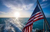 istock American Flag and Sunrise Over Gulf of Mexico 1276628084