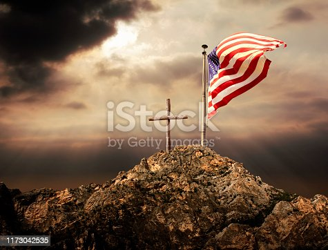 Conceptual image of waving American flag at flagpole and wooden cross over sunset sky