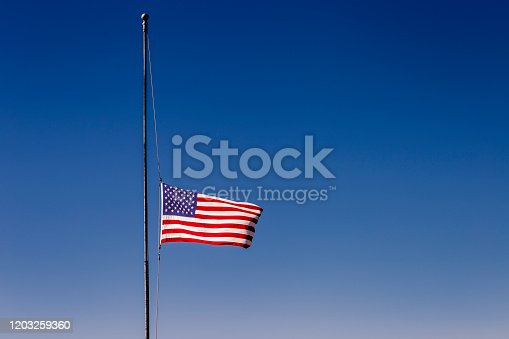 937074172 istock photo American flag at half mast, 09/11 mouning respect – United States of America 1203259360