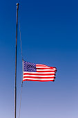 istock American flag at half mast, 09/11 mouning respect – United States of America 1203259415