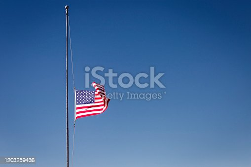 937074172 istock photo American flag at half mast, 09/11 mouning respect – United States of America 1203259436