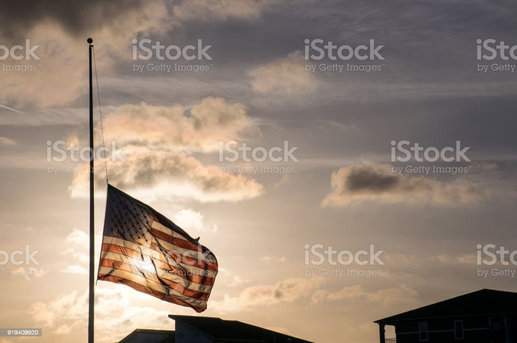 American Flag at Half Mast after another School Shooting dark future with Guns in America stock photo