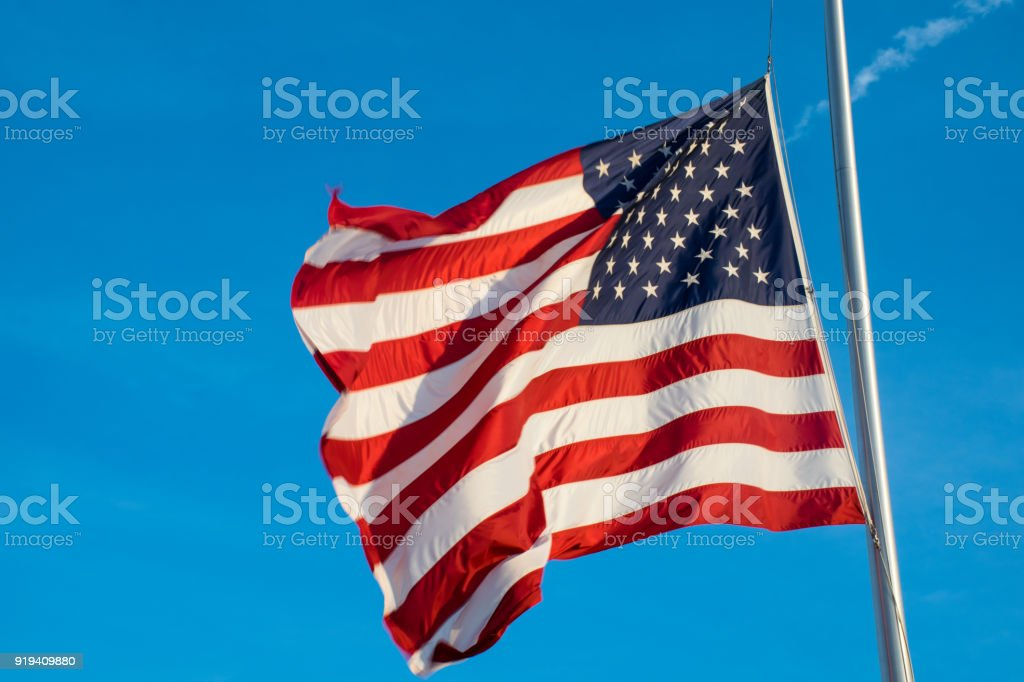 American Flag at Half Mast after another School Shooting waving in the wind with afternoon sunlight stock photo